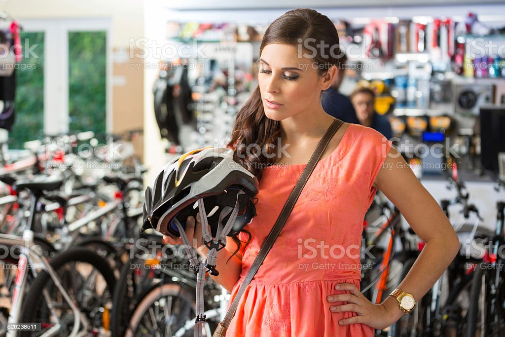 Young woman in a sports store buying helmet Close up of young woman watching the cycling helmet in bike store. 20-24 Years Stock Photo