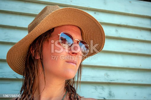 Young woman in a straw hat with sunglasses and looks forward  with glasses reflecting a small beach house