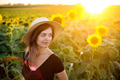 Young woman posing in a sunflower field. About 25 years old, Caucasian female.