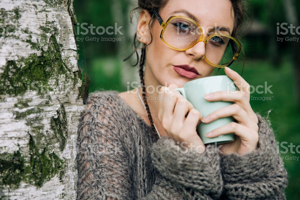 Young woman in a sweater and with glasses drinking coffee in the park royalty-free stock photo