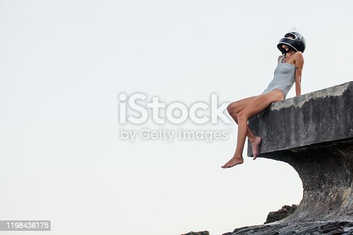 young woman in a swimsuit and a helmet sits on a stone breakwater by the sea
