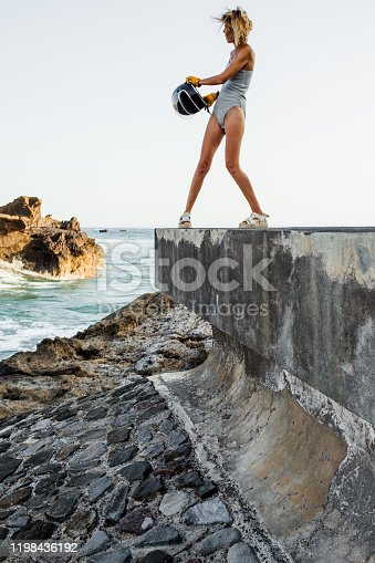 young woman in a swimsuit and a helmet is standing on a stone breakwater by the sea