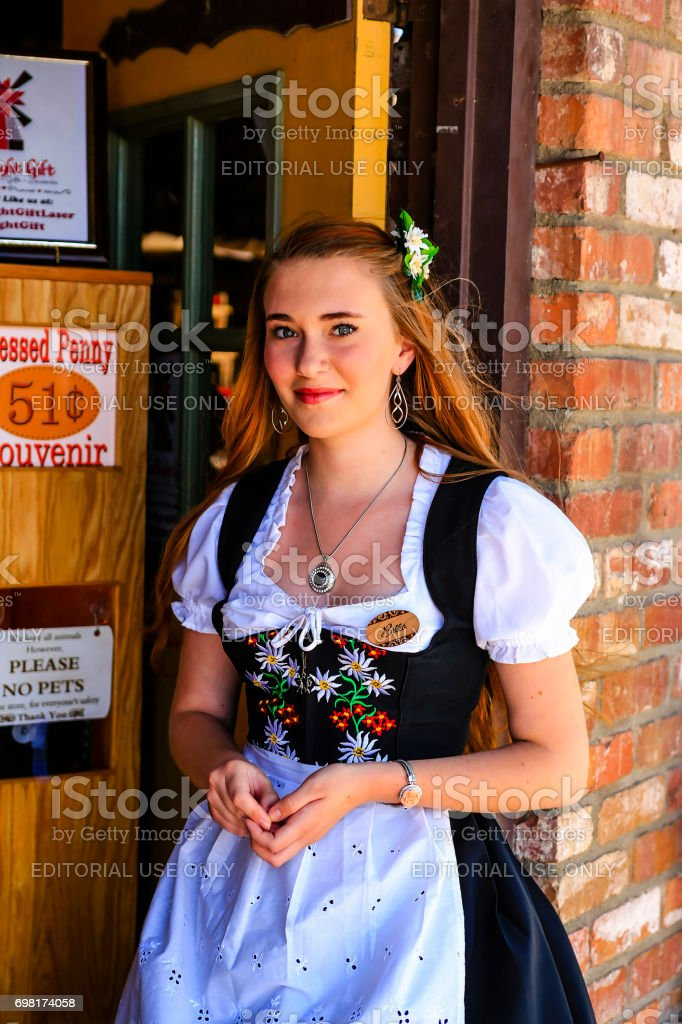 Young woman in a traditional Danish costume stands outside a store in Solvang, CA, USA stock photo