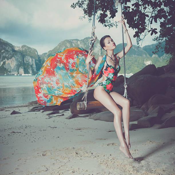 junge frau in einem baum schwingen am strand - soup_studio stock-fotos und bilder