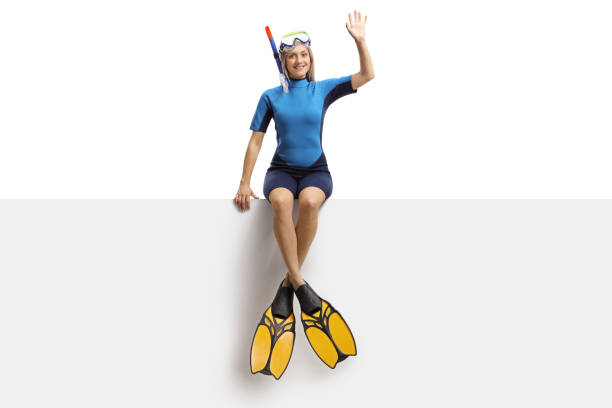 Young woman in a wetsuit, a diving mask and flippers sitting on a banner and waving Full length portrait of a young woman in a wetsuit, a diving mask and flippers sitting on a banner and waving isolated on white background diving flipper stock pictures, royalty-free photos & images