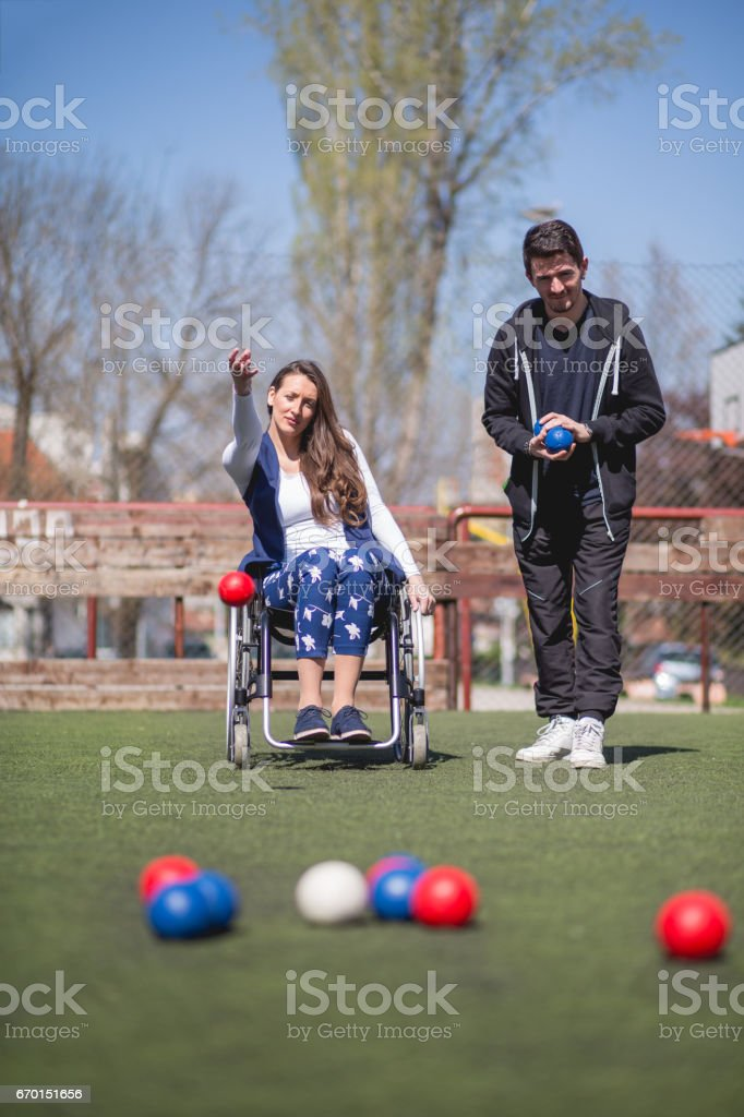 young woman in a wheelchair and his friends are playing boccia stock photo