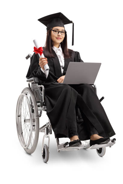 Young woman in a wheelchair wearing a graduation gown and holding a diploma and laptop stock photo
