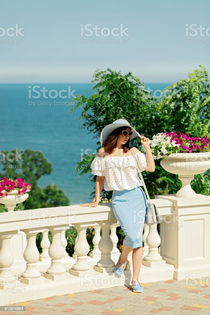 Young woman in a white blouse, blue pencil skirt and hat on a background of the sea horizon. stock photo