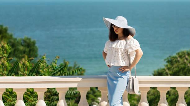 junge frau in einem weißen bluse blau bleistiftrock und hut auf einem hintergrund von den meereshorizont. - rüschenbluse stock-fotos und bilder