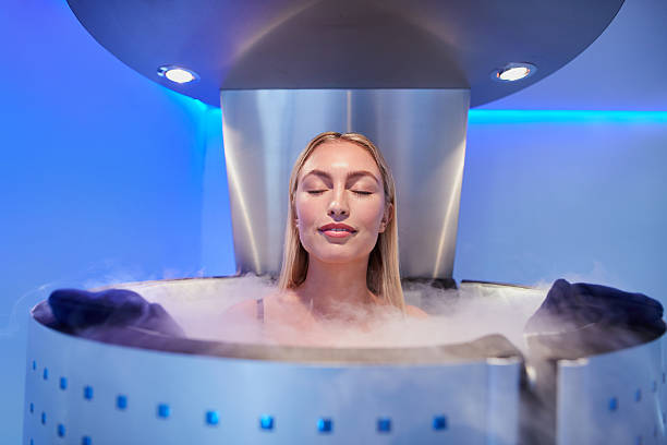 Young woman in a whole body cryotherapy cabin Portrait of happy young woman in a whole body cryotherapy cabin with her eyes closed. Cryosauna chamber for overall increase in muscular performance. cryotherapy stock pictures, royalty-free photos & images