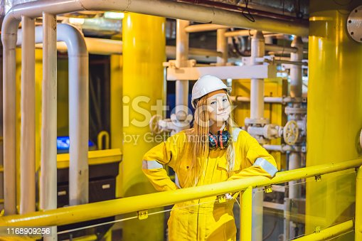Young woman in a yellow work uniform, glasses and helmet in industrial environment,oil Platform or liquefied gas plant.