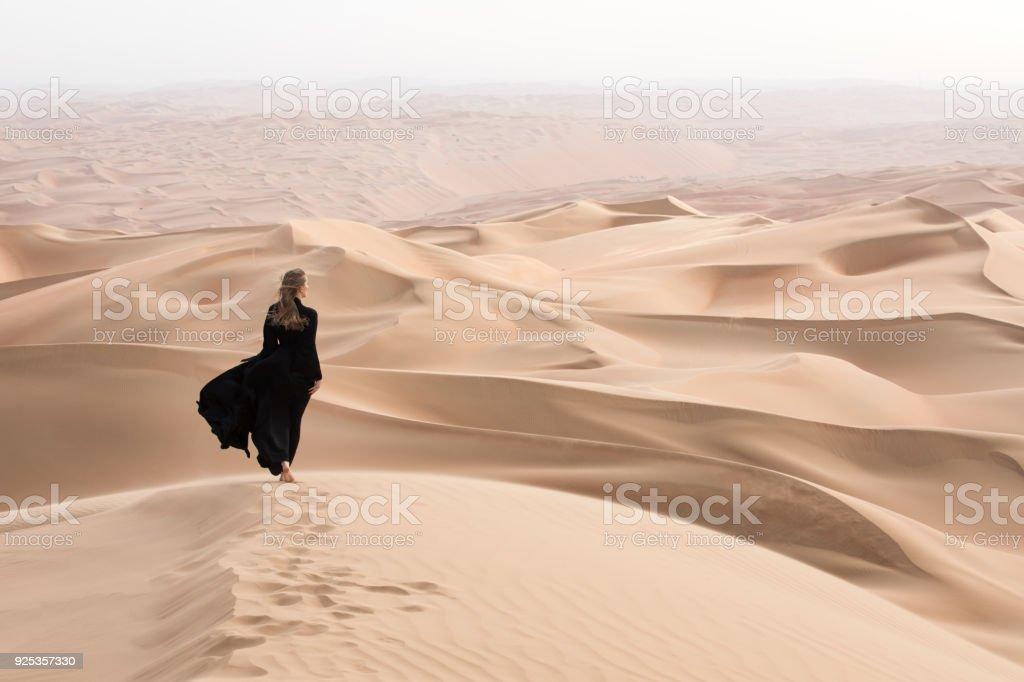 Young beautiful Caucasian woman posing in a traditional Emirati dress...