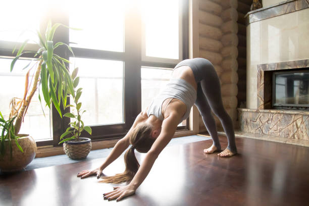 Young woman in adho mukha svanasana pose, home interior backgrou stock photo