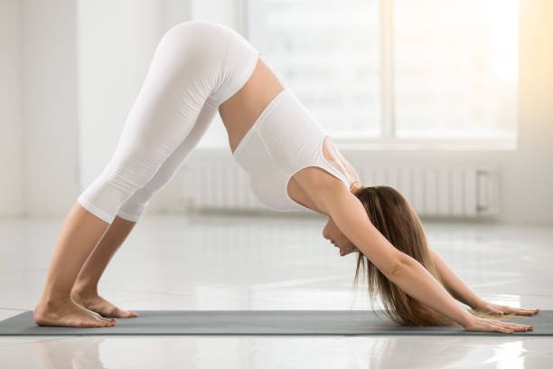 Young woman in adho mukha svanasana pose, white color background stock photo