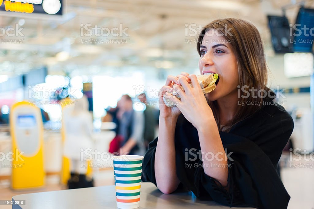 Young woman in airport, drinking coffee and eating a sandwich bildbanksfoto