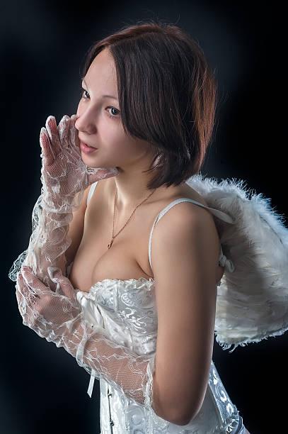 """junge frau in angel rolle etwas """"whispers"""" - damen hosen angels stock-fotos und bilder"""