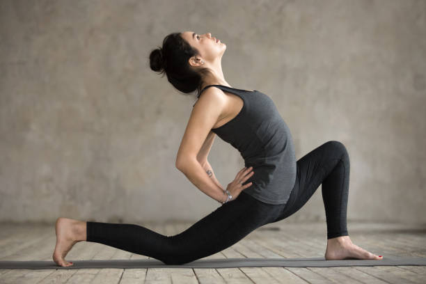 Young woman in anjaneyasana pose Young woman practicing yoga, doing Horse rider exercise, anjaneyasana pose, working out, wearing sportswear, black pants and top, indoor full length, gray wall in yoga studio sun salutation stock pictures, royalty-free photos & images