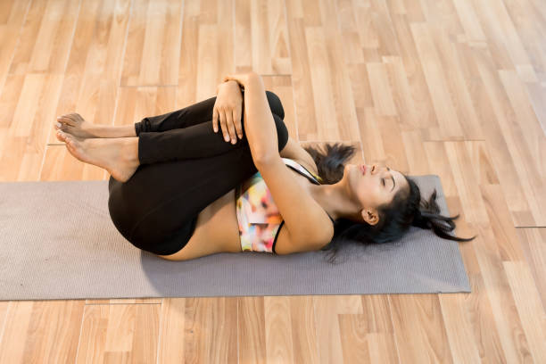 Young woman in apanasana yoga pose Fit young woman with eyes closed in apanasana yoga pose apanasana stock pictures, royalty-free photos & images