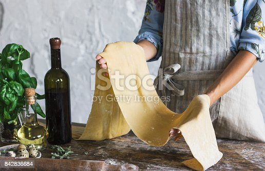 istock Young woman in apron holding the dough for homemade pasta at rustic kitchen 842836684