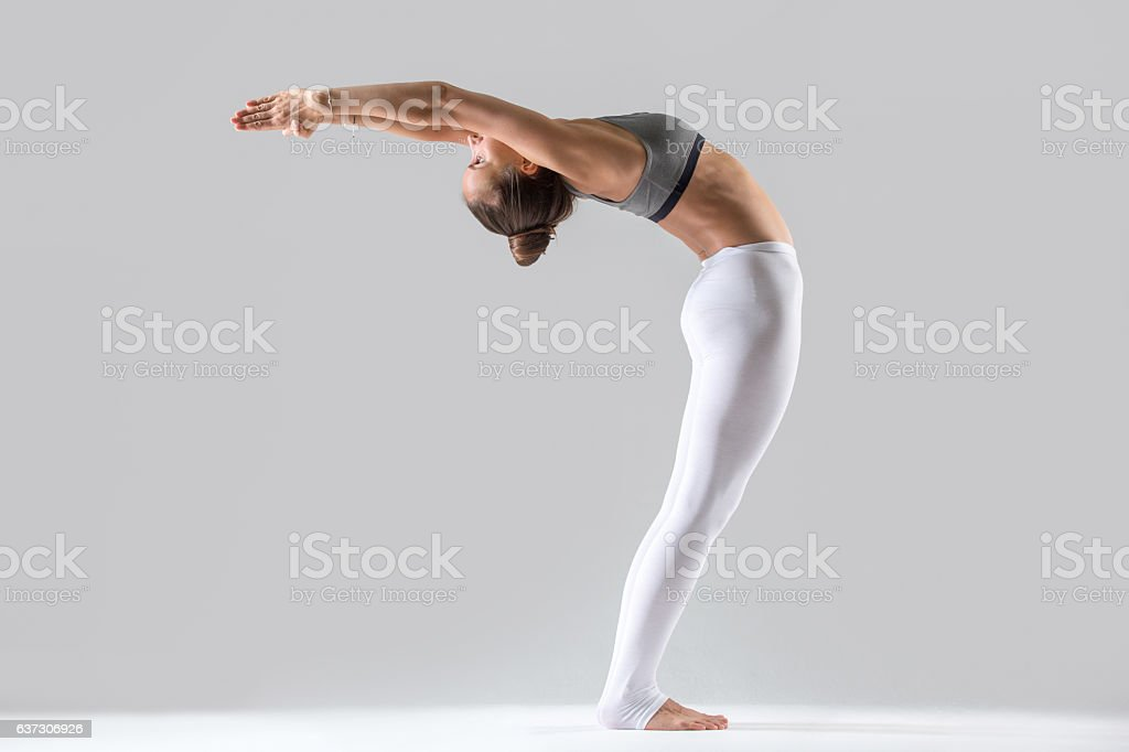 Young woman in Ardha Chakrasana pose, grey studio background stock photo