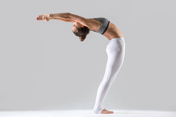Young woman in Ardha Chakrasana pose, grey studio background Young attractive woman practicing yoga, doing Standing Backward Bend exercise, Ardha Chakrasana pose, working out wearing sportswear, indoor full length, isolated, grey studio background bending over backwards stock pictures, royalty-free photos & images