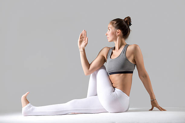 Young woman in Ardha Matsyendrasana pose, grey studio background stock photo