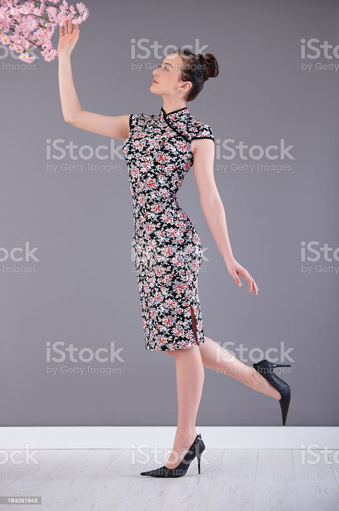 Young woman in asian outfit touching flower royalty-free stock photo