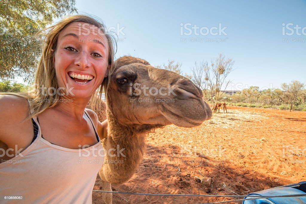 Young woman in Australia takes selfie portrait with camel stock photo