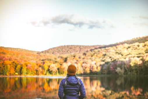 Serene young woman alone in nature surrounded by beautiful autumn colors.