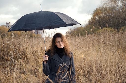 Woman hiding under umbrella from bad weather