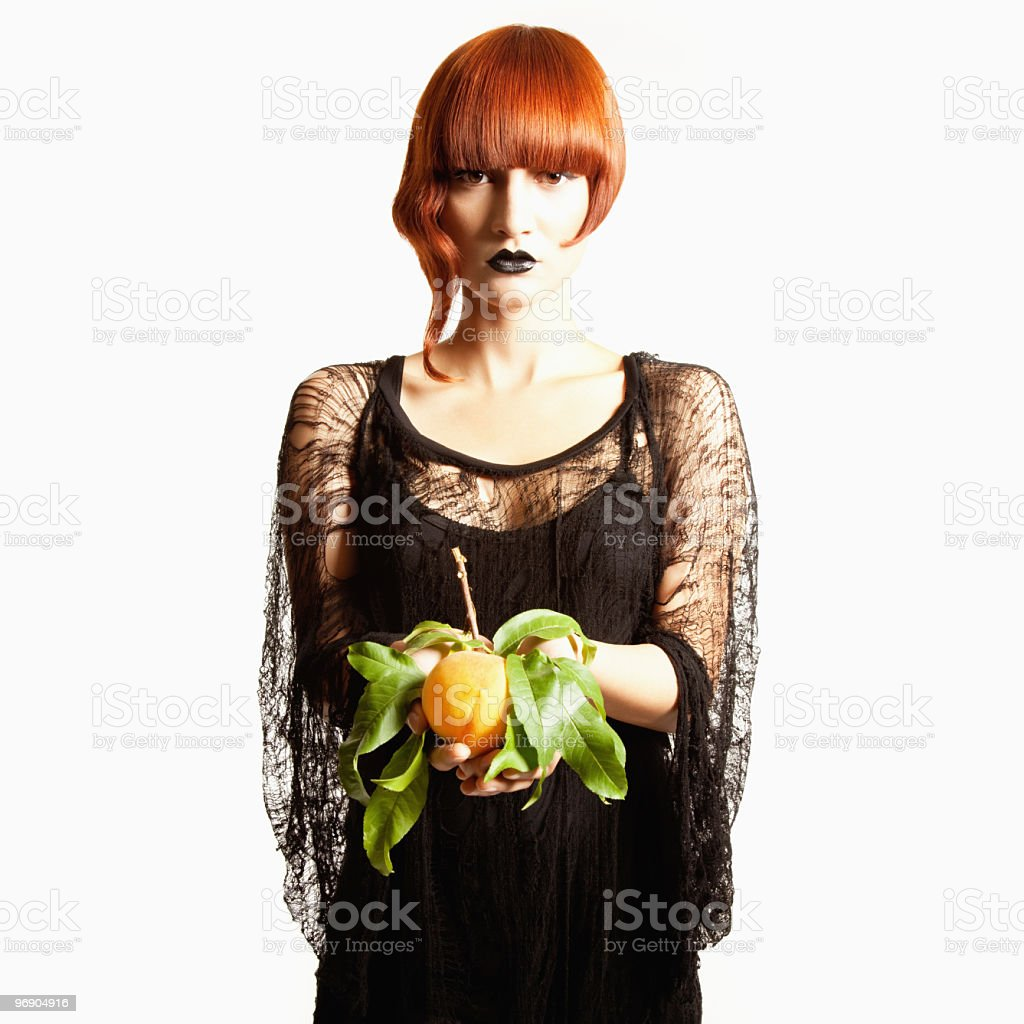 Young woman in avant-garde attire holds a peach royalty-free stock photo