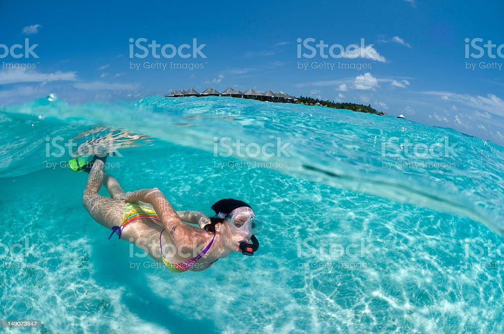 Young woman in bathing suit snorkeling in Maldives stock photo