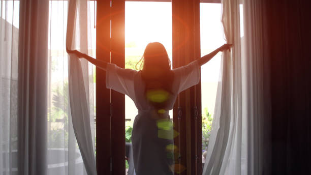 young woman in bathrobe open curtains and stretch standing near the window at home. - swim arms imagens e fotografias de stock
