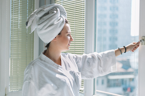 680846060 istock photo Young woman in bathrobe open curtains and stretch standing near the window at home 968247890