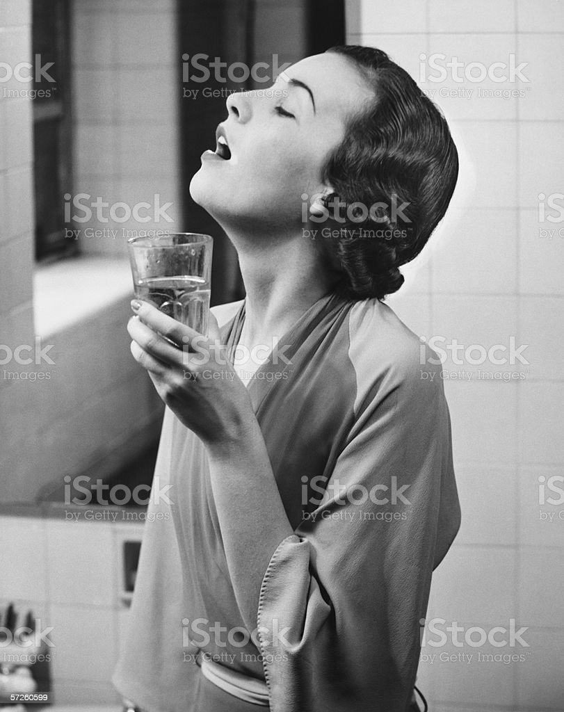 Young woman in bathroom gargling water, (B&W) stock photo