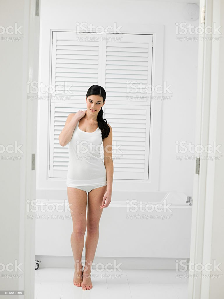 Young woman in bathroom with louvered door stock photo