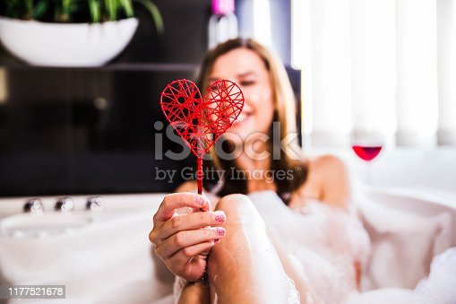 Young woman in bathtub holding red heart