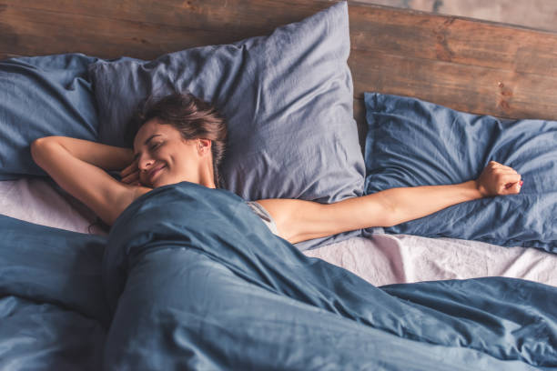 Young woman in bed Beautiful young woman is stretching and smiling while lying in bed in the morning bed furniture stock pictures, royalty-free photos & images