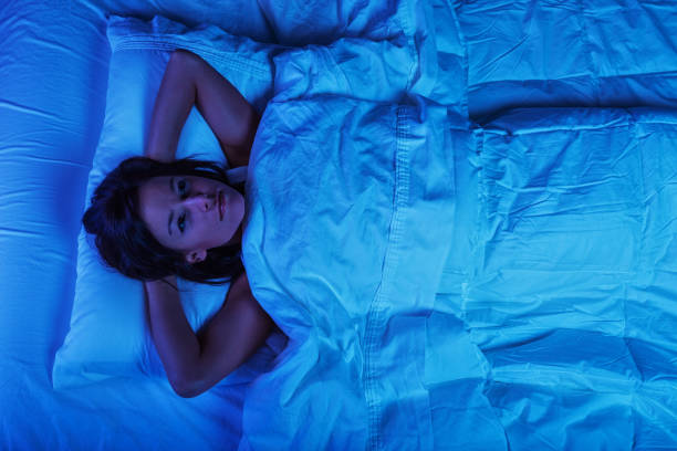 Young Woman in Bed with Insomnia stock photo