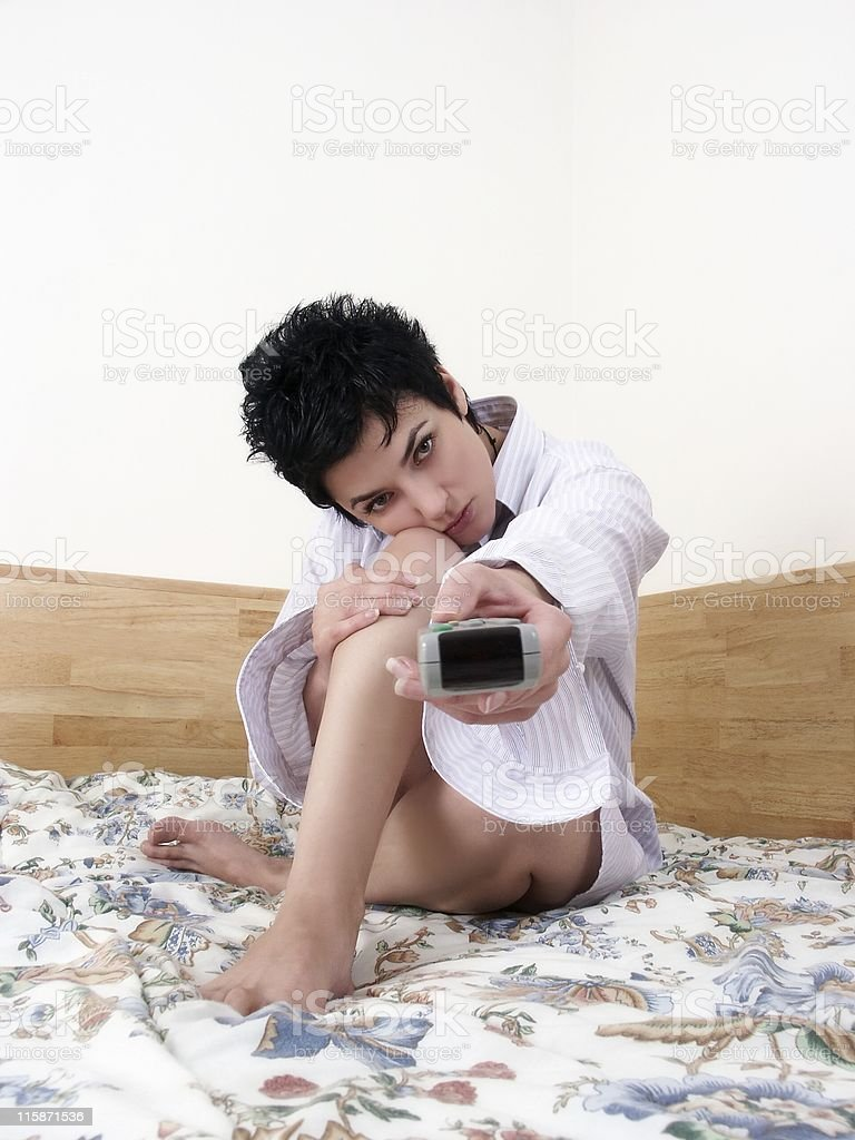 young woman in bed with remote control royalty-free stock photo