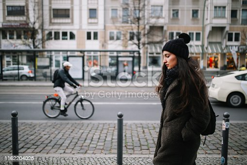 Low key portrait of a young woman wearing casual clothing, walking and in Berlin Mitte.