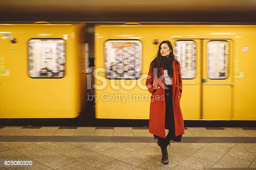 Vintage toned image of a young brunette woman wearing a red coat, standing in the Berlin metro station.