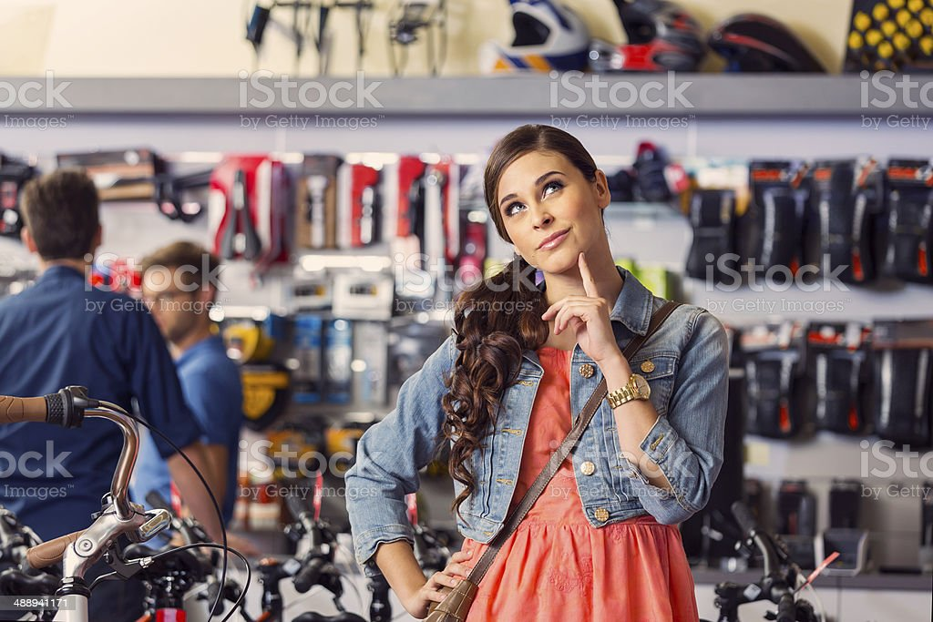 Young woman in bike store Portrait of pensive young woman standing in bike store  with two men in the background. 20-24 Years Stock Photo