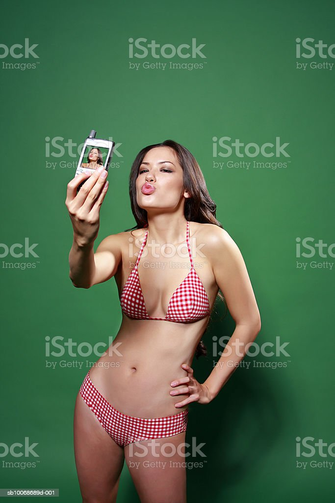 Young woman in bikini, photographing self with mobile phone royalty-free stock photo