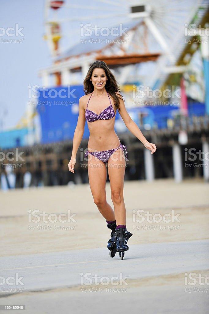 Young Woman in Bikini Rollerbladeing on Santa Monica Beach royalty-free stock photo