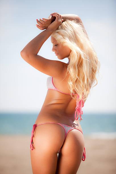 Young woman in bikini standing on beach stock photo