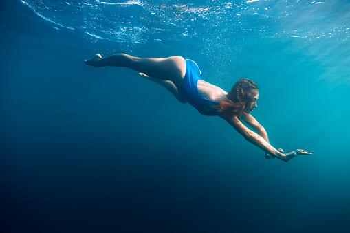 888067280 istock photo Young woman in bikini swimming in ocean 881676726