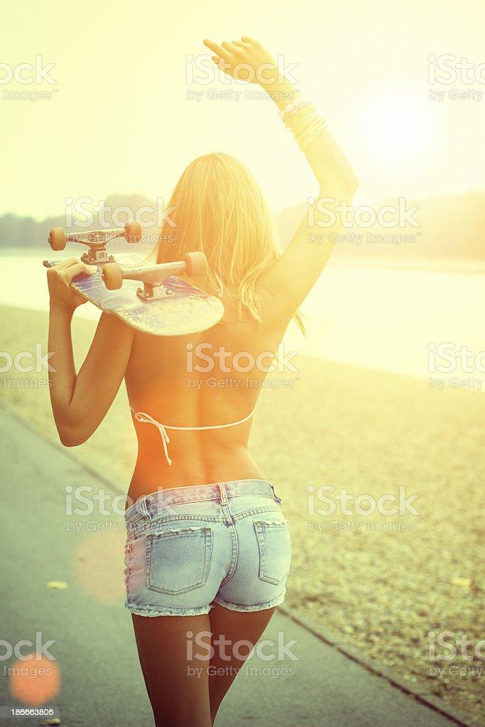 Young woman in bikini top carrying skateboard stock photo