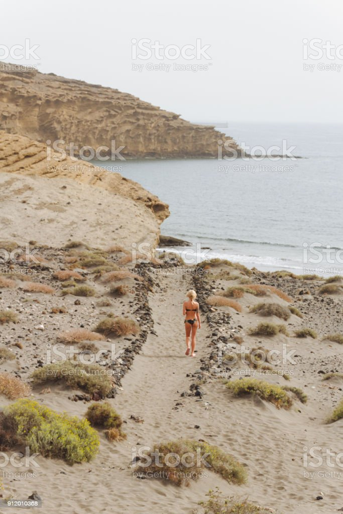 Young woman in bikini  walking through desert toward ocean - fotografia de stock