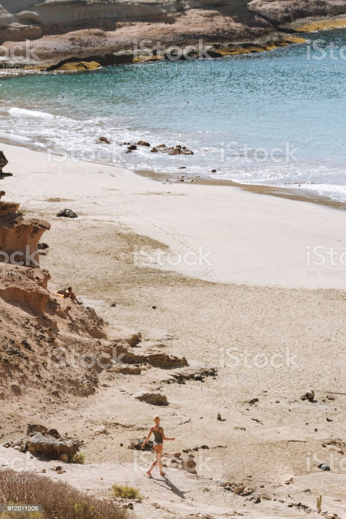 Young woman in bikini  walking toward ocean - fotografia de stock